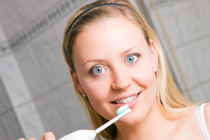 young lady with mechanical toothbrush