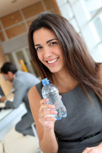 lady drinking water to help dry mouth