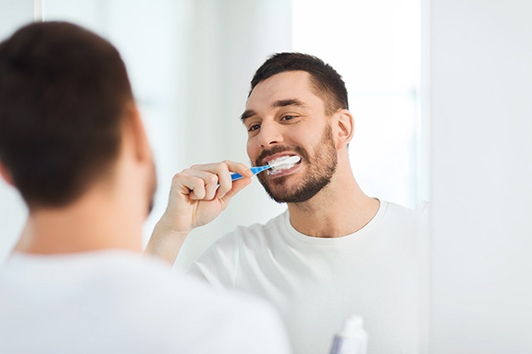 man brushing his teeth for good dental hygiene