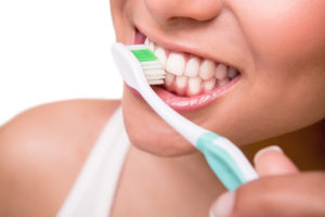 young woman with healthy teeth holding a tooth brush