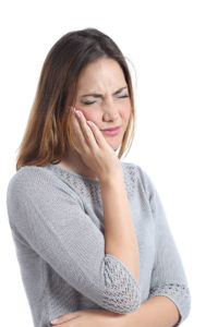 Woman suffering dental emergency with hand on face